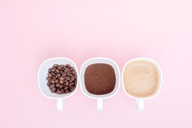 Drie kopjes verschillende stadia van koffiebereiding of het maken van koffiedrank geïsoleerd op roze