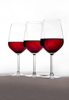 Drie kristallen glazen in harmonie en vol wijn op een witte achtergrond