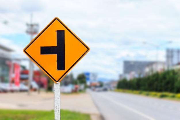Drie kruising geel verkeersbord met soft-focus en overbelichting op de achtergrond