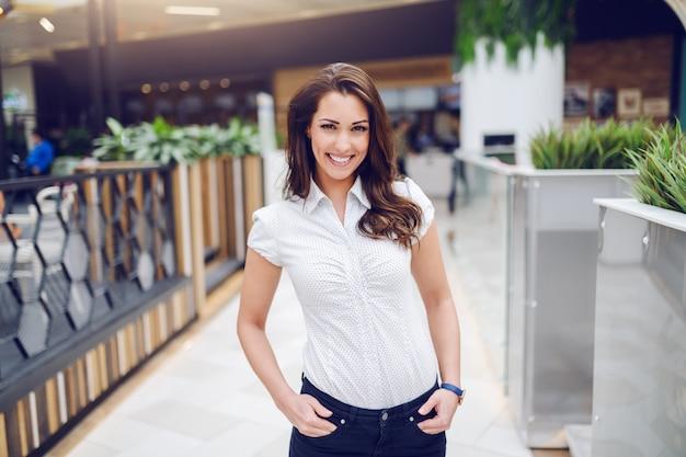 Drie kwart lengte van prachtige kaukasische brunette in overhemd poseren in winkelcentrum.