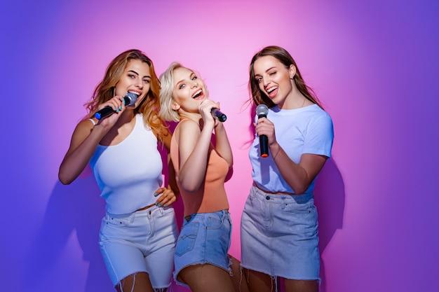 Drie lachende jonge meisjesband zingt liedjes in de microfoon