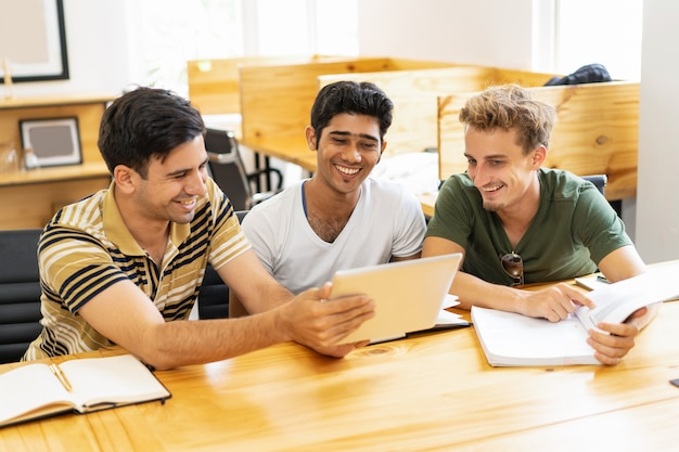 Drie lachende studenten die bestuderen, die op tablet doorbladeren