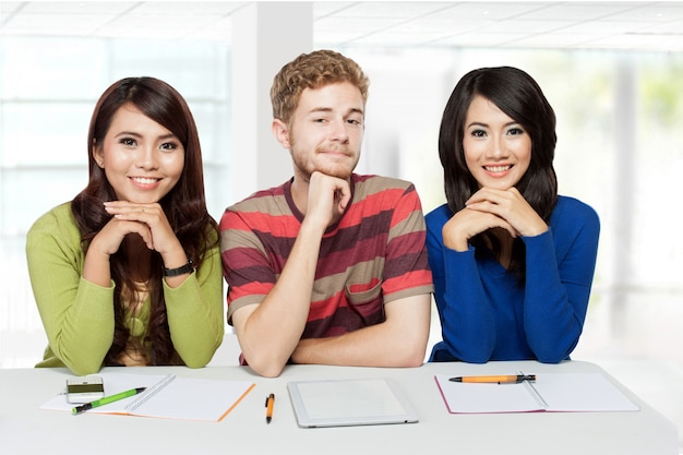 Drie lachende studenten samen studeren