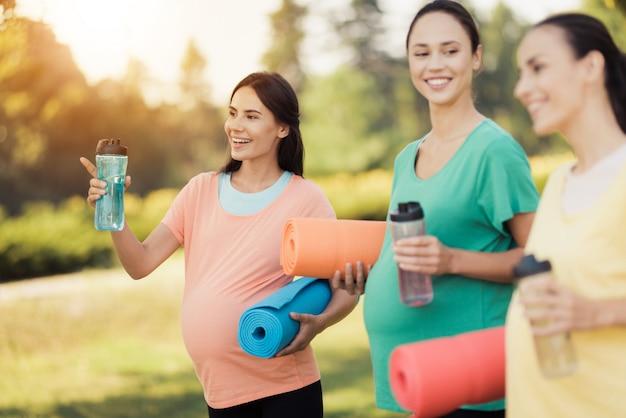 Drie lachende zwangere meisjes met yogamatten.