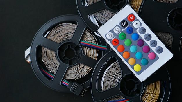 Drie led strip spoelen close-up. diode met bedieningspaneel voor het wisselen van kleuren op donkere achtergrond.