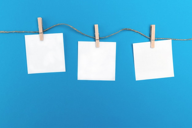 Drie lege kleine vellen papier houden door houten wasknijpers aan een touwtje