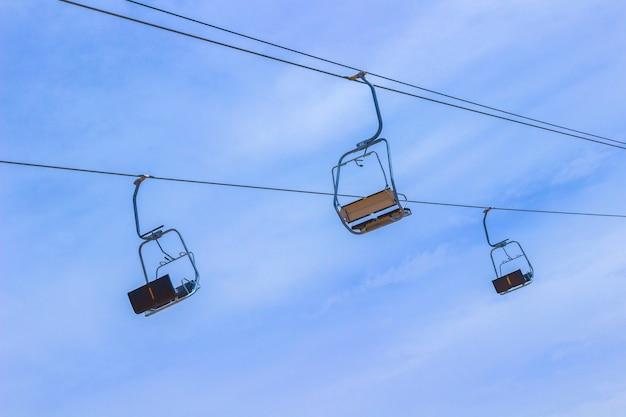 Drie lege liftstoel tegen de hemel