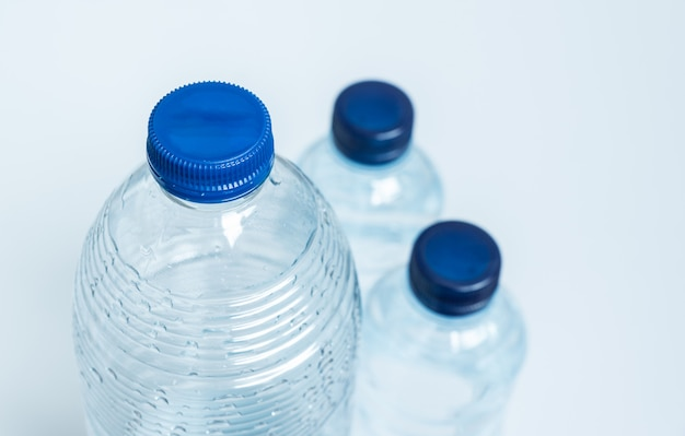 Drie lege plastic flessen met blauwe doppen