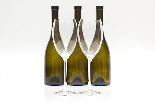 Drie lege wijnflessen en twee glazen op een witte achtergrond.