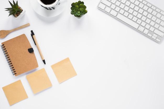 Drie lege zelfklevende notities met dagboek; pen en toetsenbord op witte achtergrond