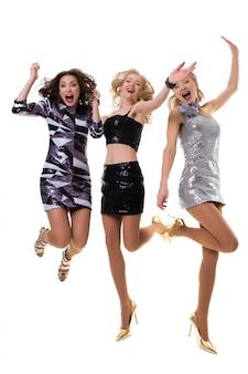 Drie leuke europese meisjes die in de studio op wit in glanzende geïsoleerde kleding dansen -