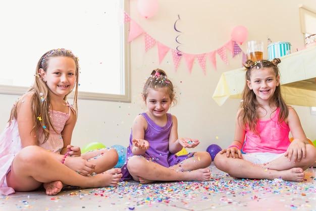 Drie leuke meisjes die op vloer zitten die in een partij genieten van