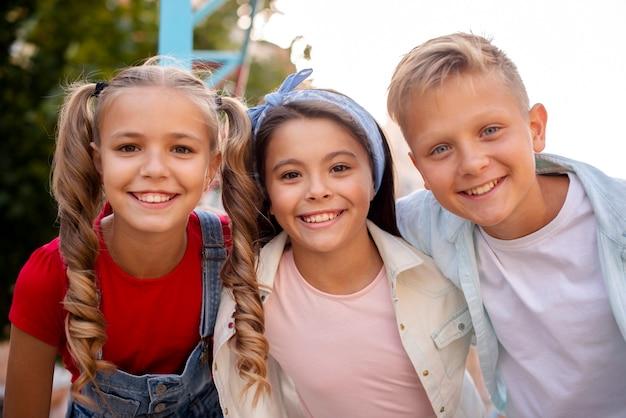 Drie leuke vrienden die op de speelplaats glimlachen