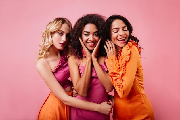 Drie leuke vrouwen die samen op roze muur stellen