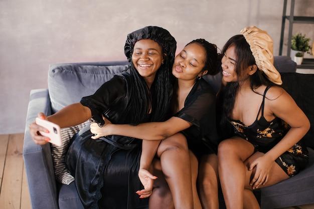 Drie lichaams positieve afro-amerikaanse meisjes die op de bank zitten, worden aan de telefoon gefotografeerd