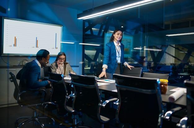 Drie managers die in nachtbureau werken. mannelijke en vrouwelijke werknemers, donker zakencentrum interieur, moderne werkplek modern