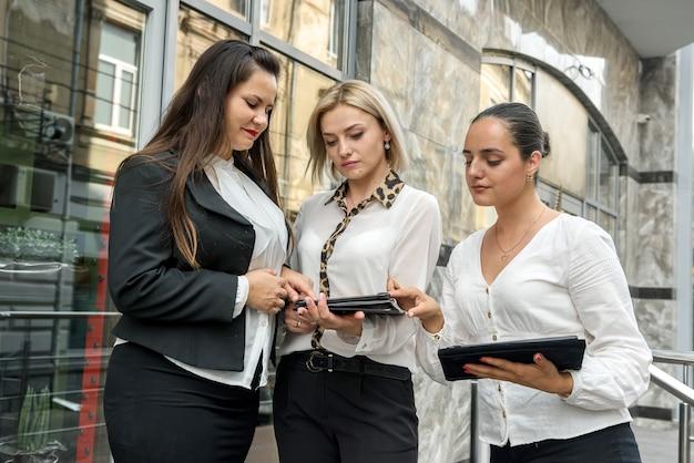 Drie managers met mappen poseren buiten kantoorgebouw