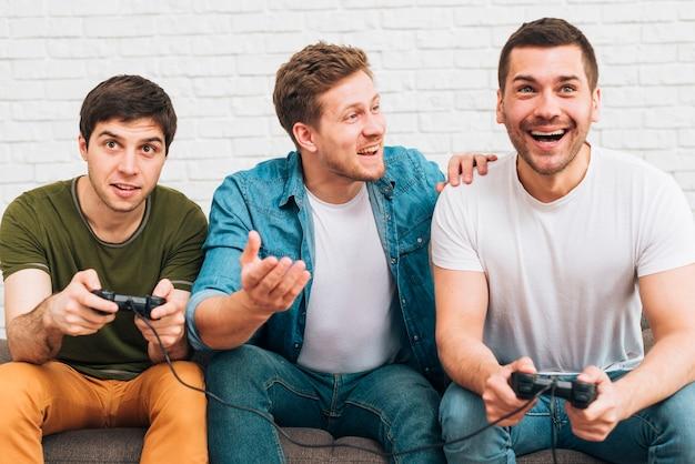 Drie mannelijke vrienden die samen van het videogame zitten genieten