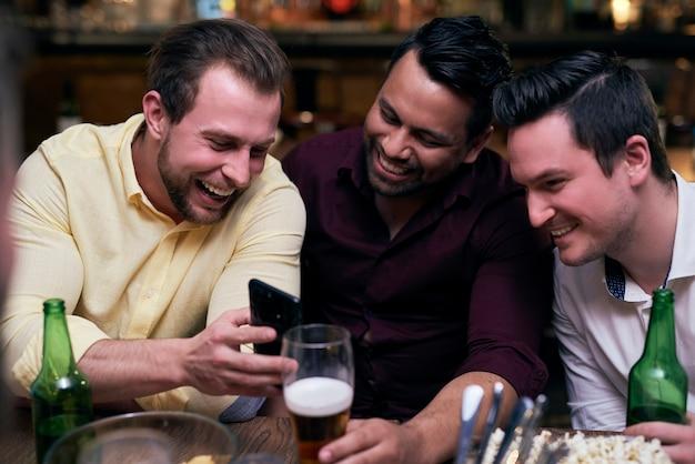 Drie mannen die mobiele telefoon gebruiken tijdens een ontmoeting in de kroeg