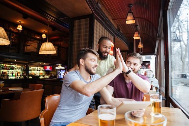 Drie mannen vrienden kijken samen naar wedstrijd op tablet in bar en geven high five