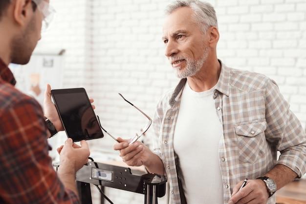 Drie mannen zetten een zelfgemaakte 3d-printer op om het formulier af te drukken.