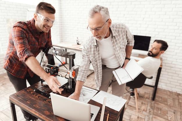 Drie mannen zetten een zelfgemaakte 3d-printer op om het formulier af te drukken