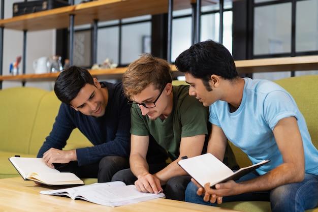Drie medestudenten die een leerboek lezen en zich voorbereiden op een examen