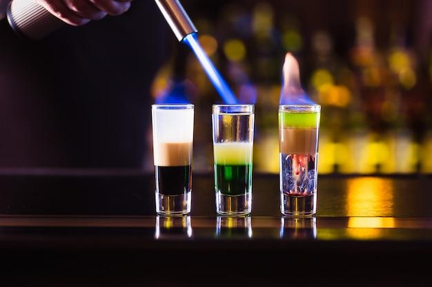Drie meerlagige brandende cocktail. de barman steekt ze lichter aan.