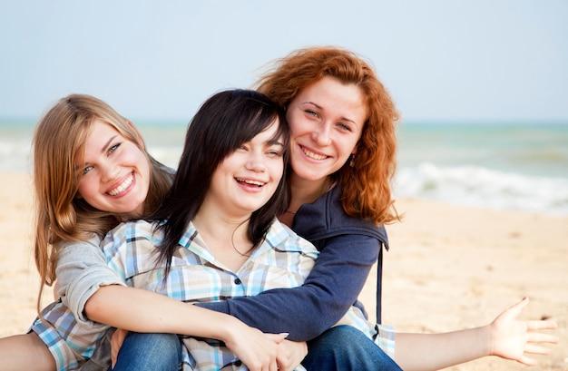 Drie meisjes bij openlucht dichtbijgelegen strand.