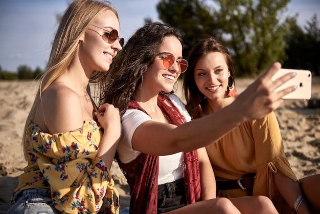 Drie meisjes die een selfie maken op het strand