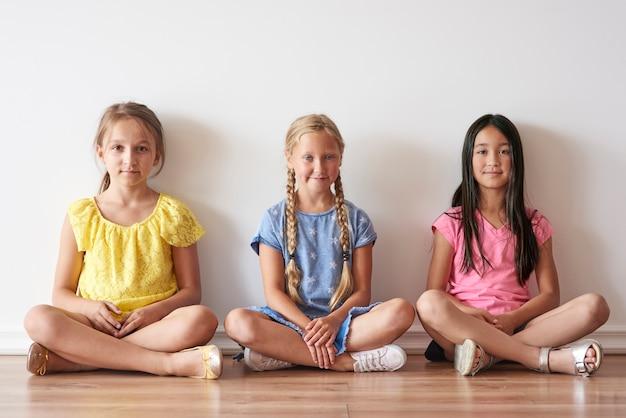 Drie meisjes die met gekruiste benen zitten