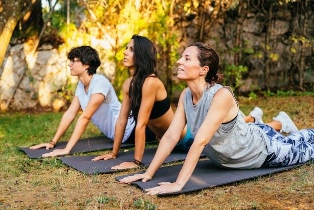 Drie meisjes die yogahouding maken.