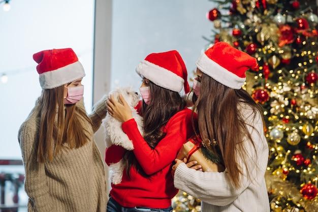 Drie meisjes en een terriër poseren voor de camera op oudejaarsavond. kerstmis tijdens coronavirus, concept
