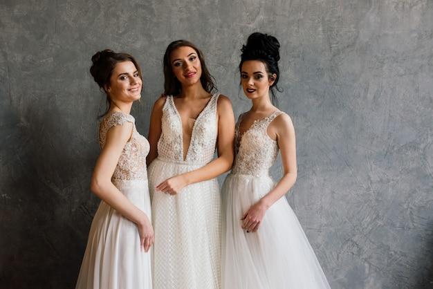 Drie meisjes in de studio in elegante witte jurken