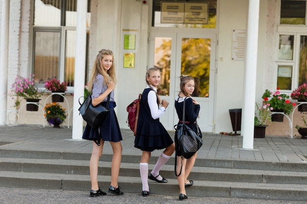 Drie meisjes in schooluniform met rugzakken staan op de trap voor de school