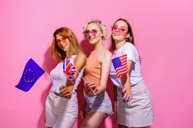 Drie meisjes in zomerklerenglazen met vlaggen van de europese unie, verenigde staten en brittannië...