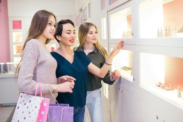 Drie meisjes kijken naar showcase op winkelen in het winkelcentrum
