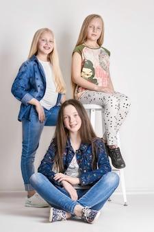 Drie meisjes poseren, een modelschool voor kinderen