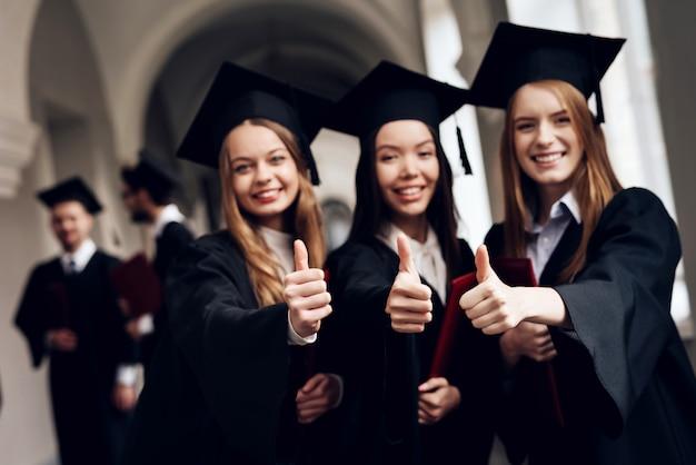 Drie meisjes poseren voor een camera op de universiteit.