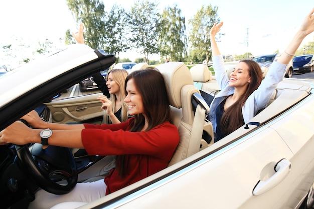 Drie meisjes rijden in een cabriolet en hebben plezier