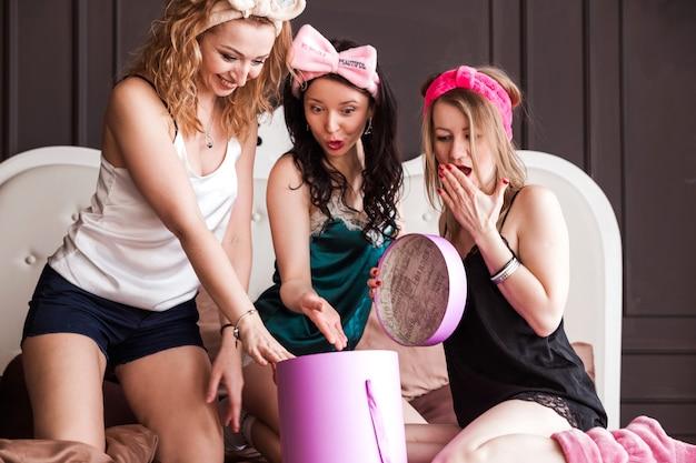 Drie meisjes van een vriend gooiden een pyjamafeestje op een zacht bed. de meisjes glimlachen en openen samen de doos met een verrassing.