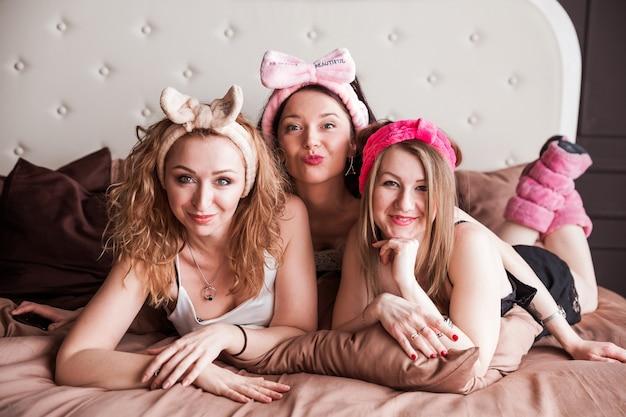 Drie meisjes van een vriend gooiden een pyjamafeestje op een zacht bed. meisjes glimlachen en kijken naar de camera.