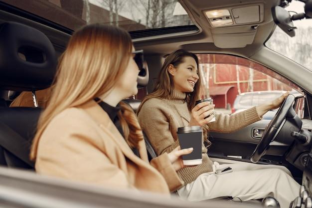 Drie meisjes zitten in de auto en het drinken van een kopje koffie