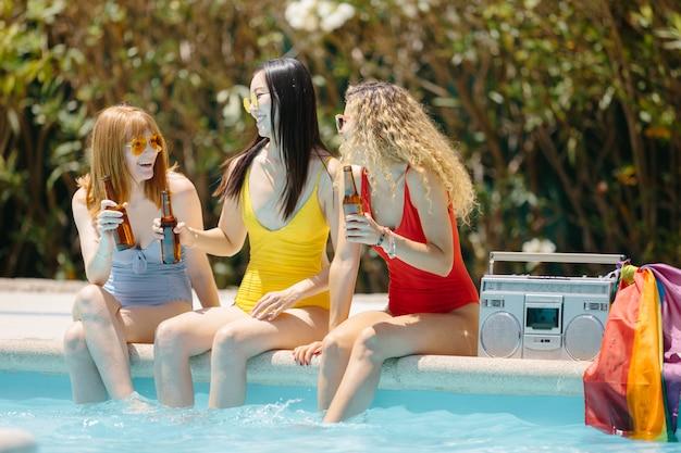 Drie meisjes zitten in een zwembad bier drinken met een cassette en een lgtb-vlag