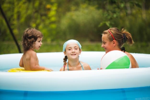 Drie meisjes zwemmen in het blauwe zwembad en spelen met de bal