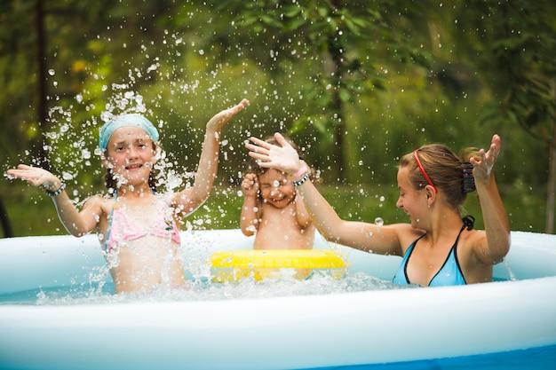 Drie meisjes zwemmen in het blauwe zwembad en spelen