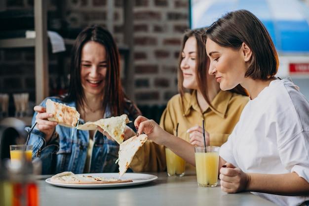 Drie meisjesvrienden die pizza hebben bij een bar