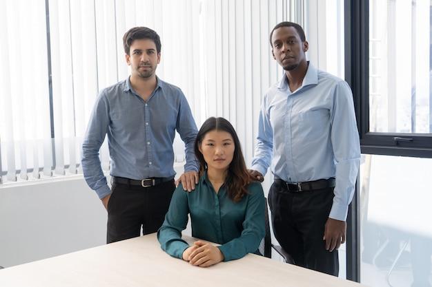Drie mengelings reed beambten die in modern bedrijfsbinnenland stellen.