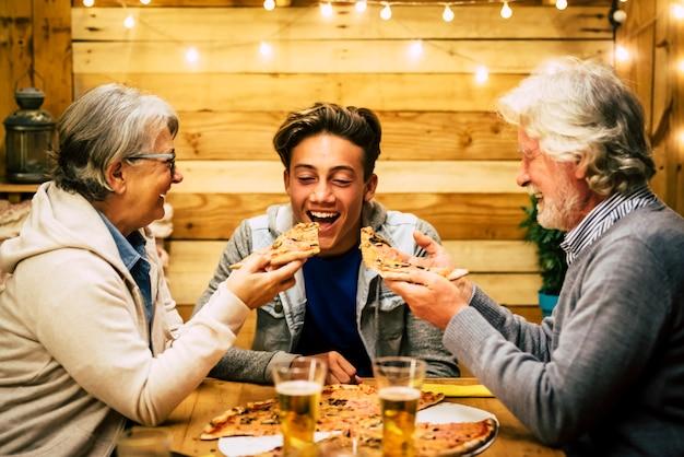 Drie mensen aan tafel met pizza - twee senioren die proberen te eten bij de tienerpizza - vieren nieuwjaar of een feestje samen