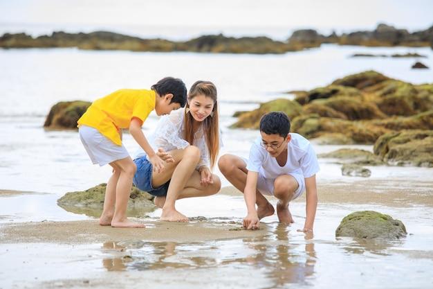 Drie mensen aziatische familie, moeder en zonen, die op tropisch strand spelen